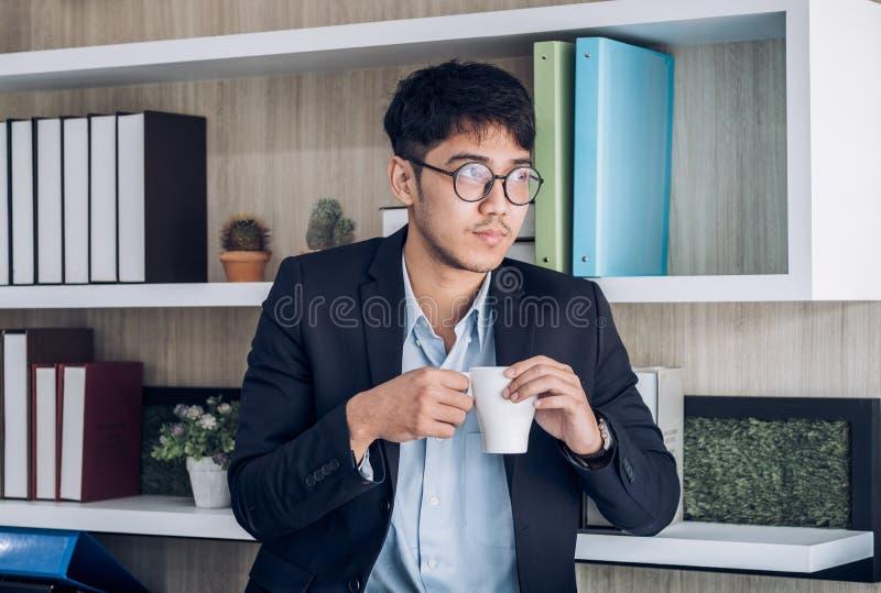 Café asiático da bebida do homem de negócios no escritório tome um breake do trabalho duro com relaxam a emoção imagens de stock royalty free