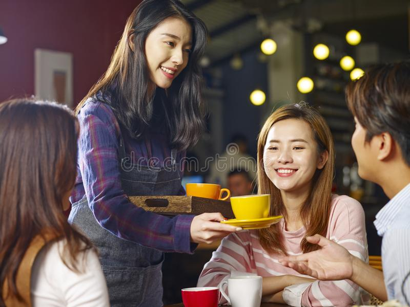 Café asiático sonriente de la porción de la camarera de los jóvenes a los clientes foto de archivo