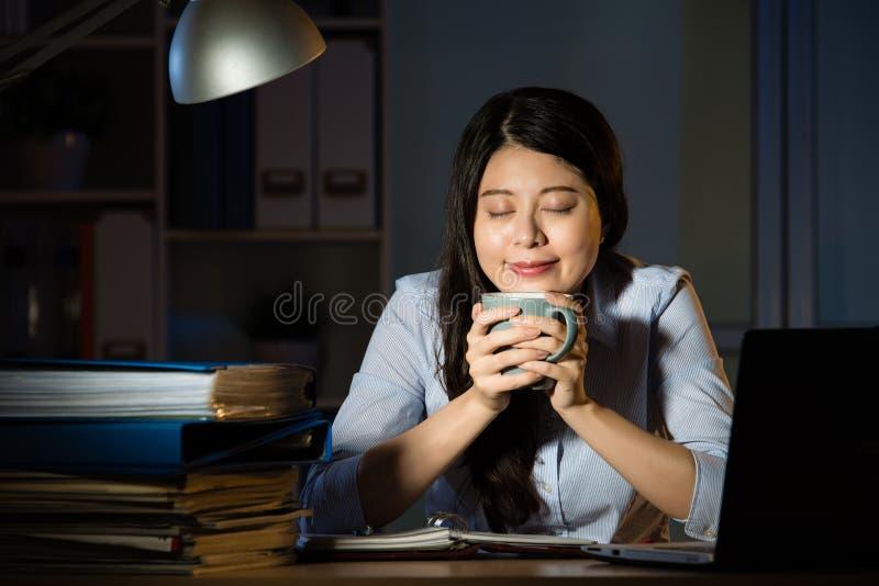 Café asiatique de boissons de femme d'affaires fonctionnant des heures supplémentaires de fin de nuit photos libres de droits