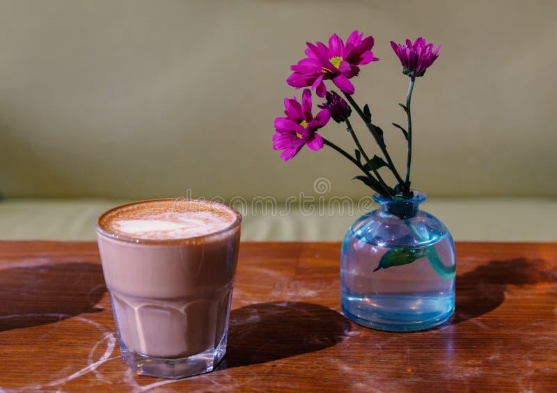 caf? australiano Liso-branco em tabletop gasto com as flores vermelhas na garrafa azul fotografia de stock