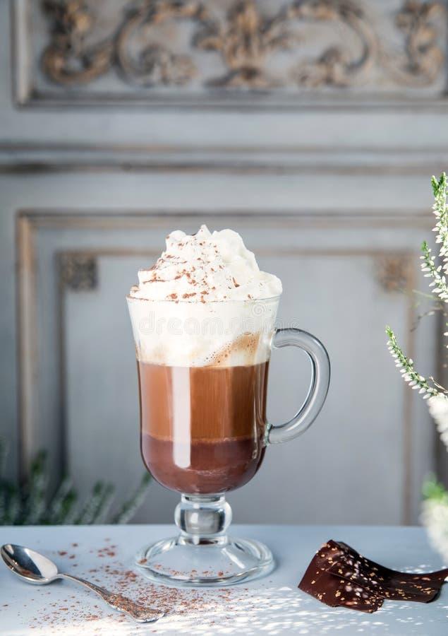 Café avec du chocolat et la crème fouettée dans un verre transparent dans la perspective d'un mur de cru images stock