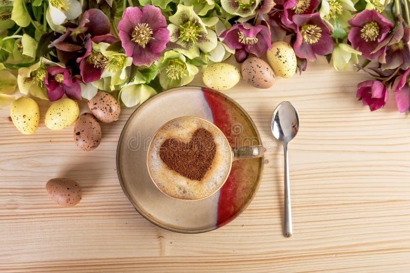 Café avec la forme de coeur et décoration de Pâques de fleurs sur la table en bois image stock