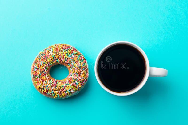 Café avec le beignet sur le fond bleu Vue sup?rieure images stock