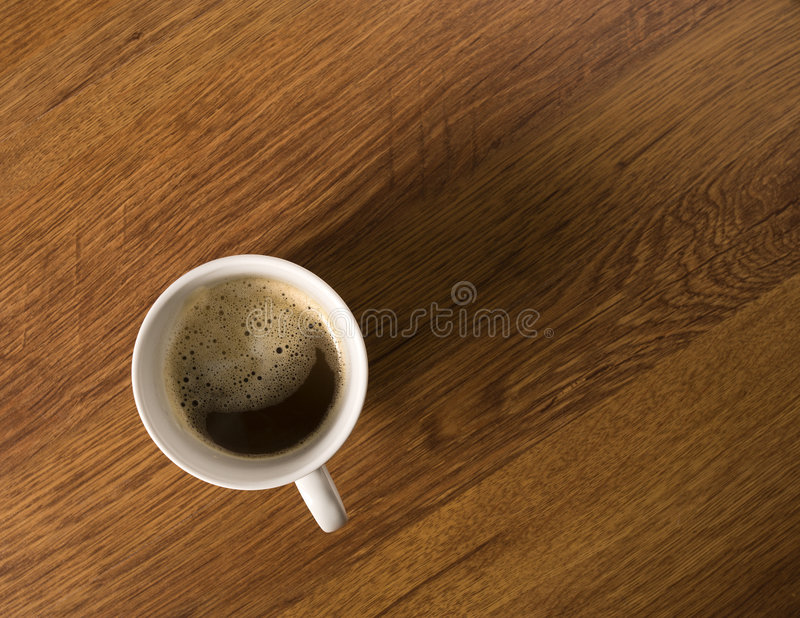 Café avec le crema dans la tasse blanche sur l'appareil de bureau en bois, photos stock