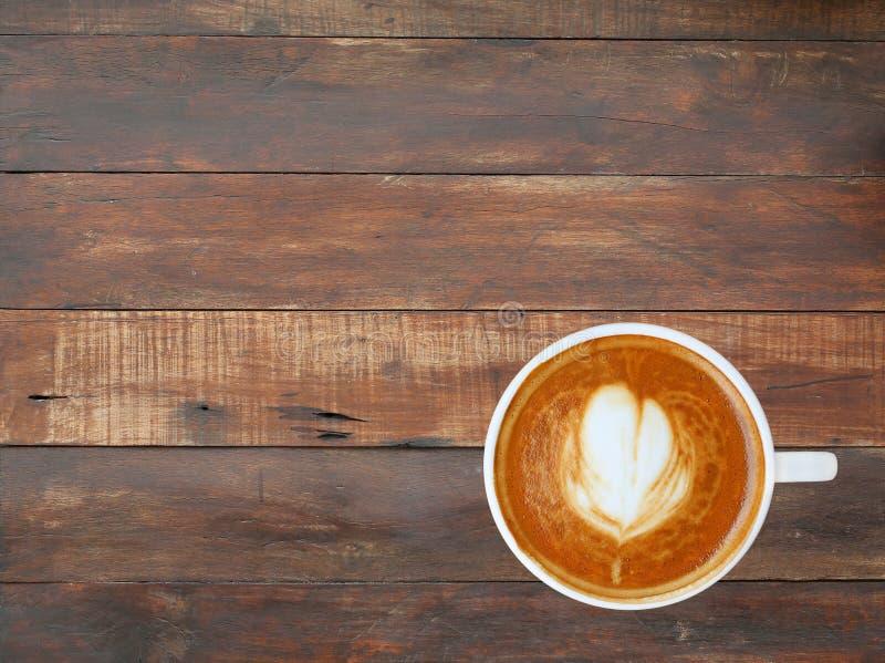 Café avec le modèle de coeur dans une tasse blanche sur le fond en bois fin de planche photos stock