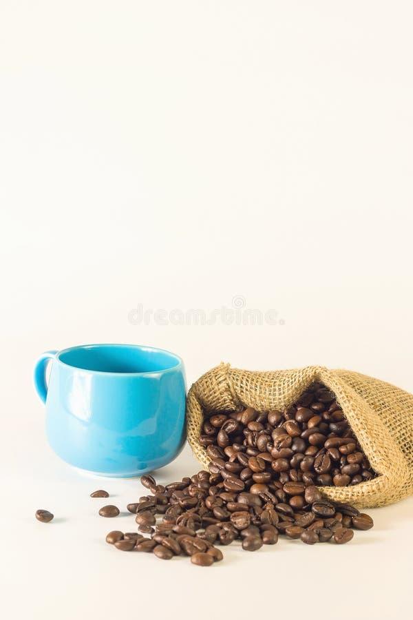 Café azul de la taza con los sacos del bolso de granos de café en el fondo blanco fotografía de archivo libre de regalías