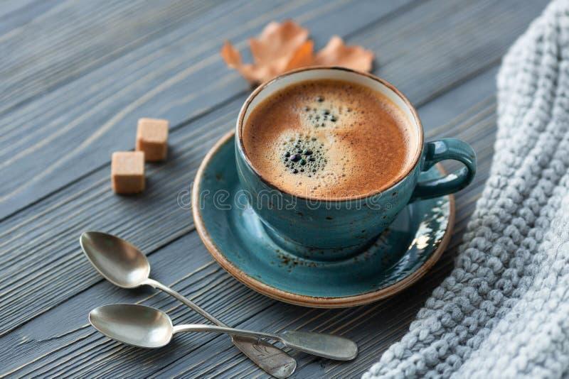 Café azul del whith de la taza, suéter hecho punto, hojas de otoño en fondo de madera imagenes de archivo