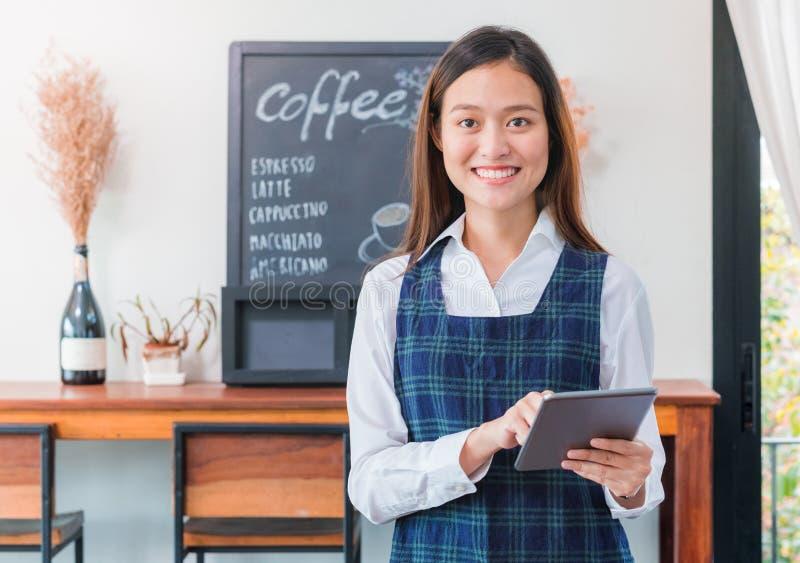 Café azul do tablet pc da posse do avental do desgaste fêmea asiático do barista imagem de stock
