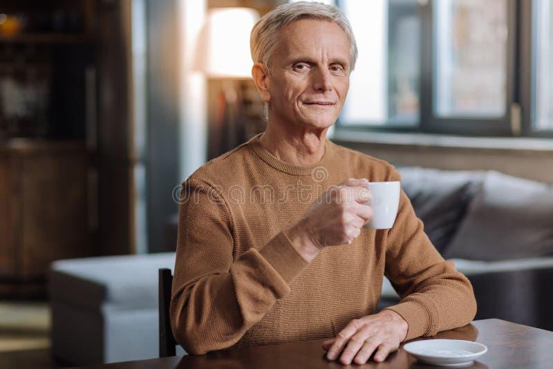 Café bebendo agradável calmo do homem superior em casa foto de stock