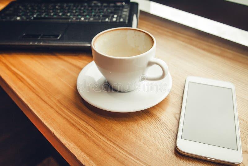 Café bebendo ao usar um portátil no café Café terminado com telefone e portátil na fonte da janela imagens de stock