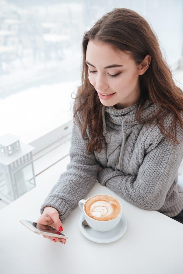 Café bebendo da jovem mulher atrativa ao conversar pelo telefone imagens de stock royalty free