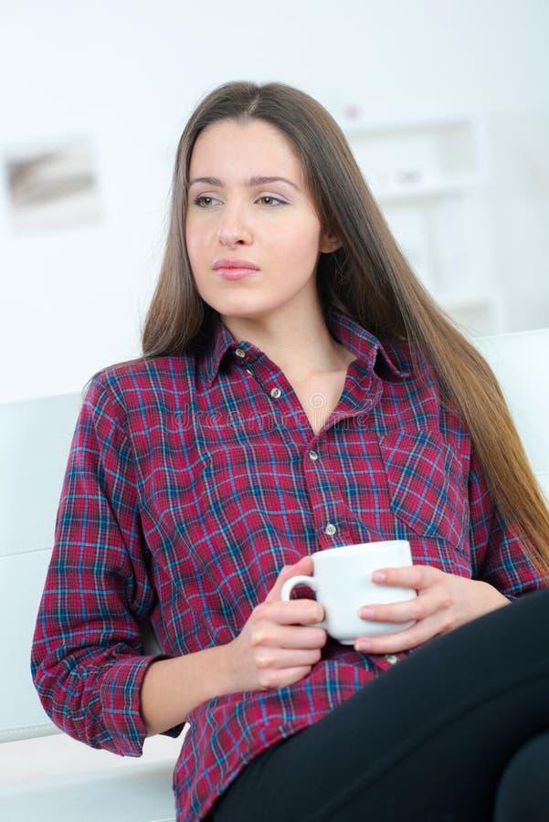 Café bebendo da jovem mulher com expressão pensativa na cara imagens de stock royalty free