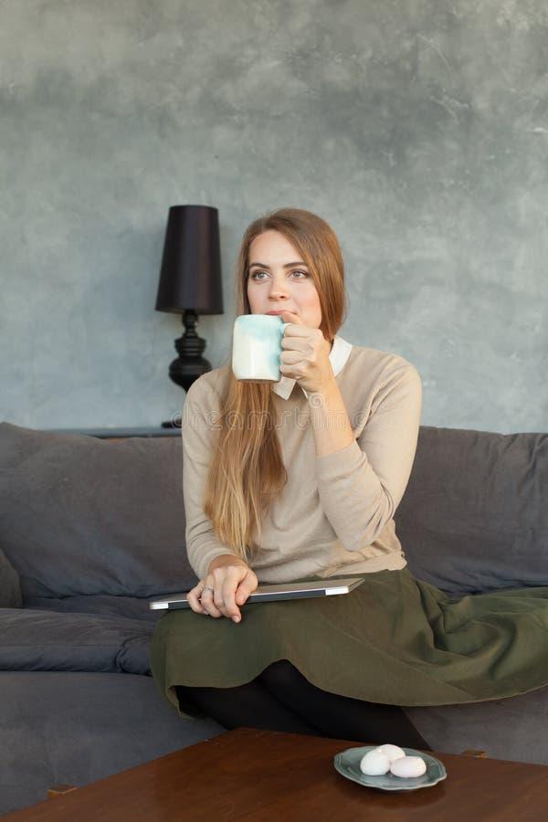 Café bebendo da jovem mulher em casa foto de stock