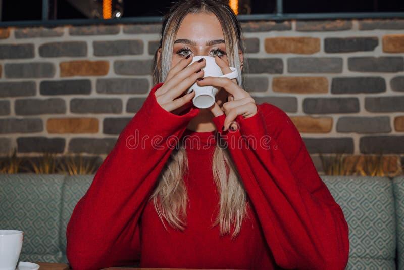 Café bebendo da jovem mulher em um café imagens de stock royalty free