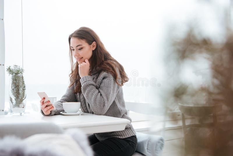 Café bebendo da jovem senhora bonita ao conversar pelo telefone fotografia de stock