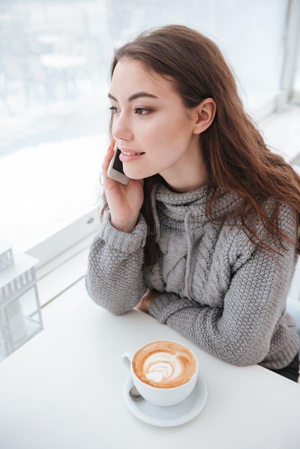 Café bebendo da jovem senhora bonita ao falar pelo telefone imagens de stock