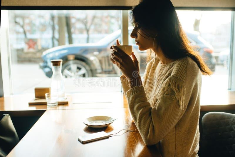 Café bebendo da menina e escuta a música fotos de stock