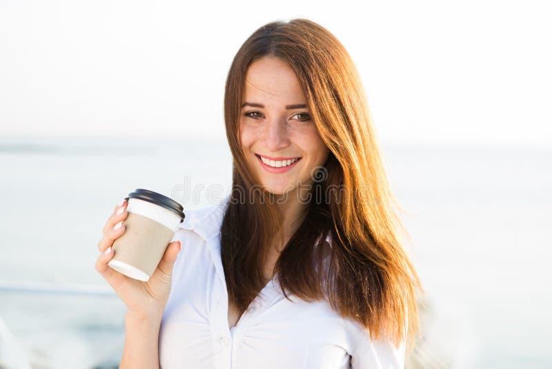 Café bebendo da menina 'sexy' nova no beira-mar fotografia de stock