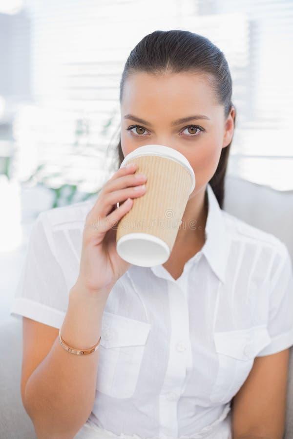 Café bebendo da mulher bonita relaxado que senta-se no sofá confortável fotos de stock royalty free