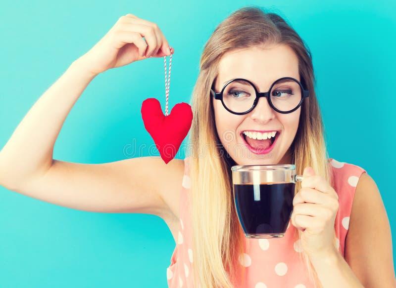 Café bebendo da mulher com um coxim do coração foto de stock royalty free