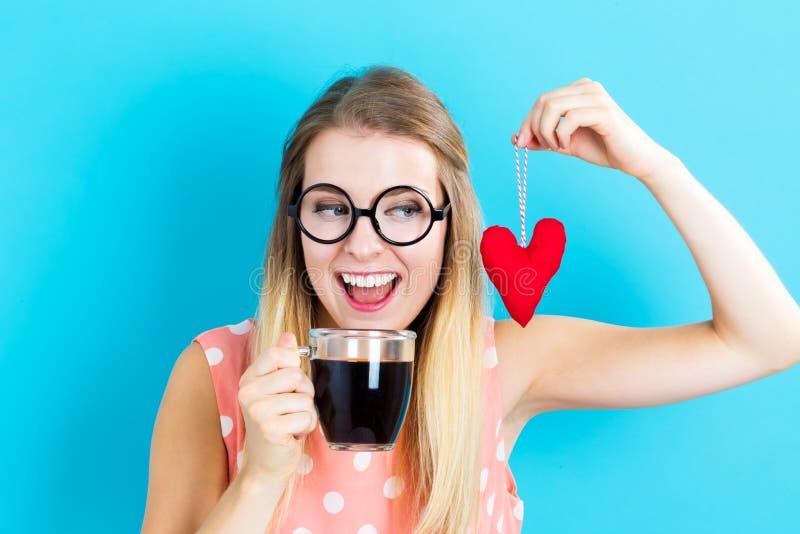 Café bebendo da mulher com um coxim do coração foto de stock