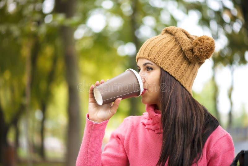 Café bebendo da mulher do outono no banco de parque sob a folhagem de outono imagem de stock royalty free