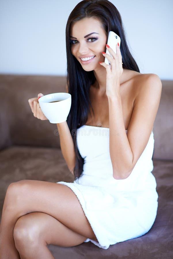 Café bebendo da mulher e conversa em um móbil fotos de stock
