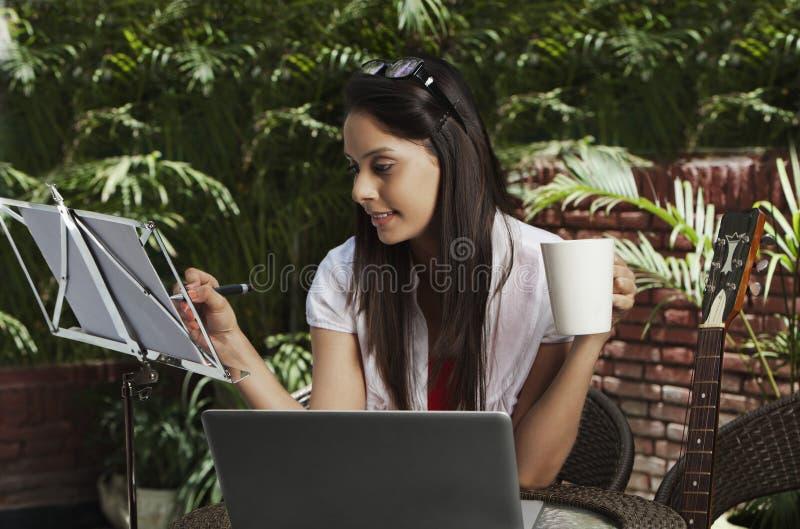 Café bebendo da mulher e utilização de um portátil imagem de stock