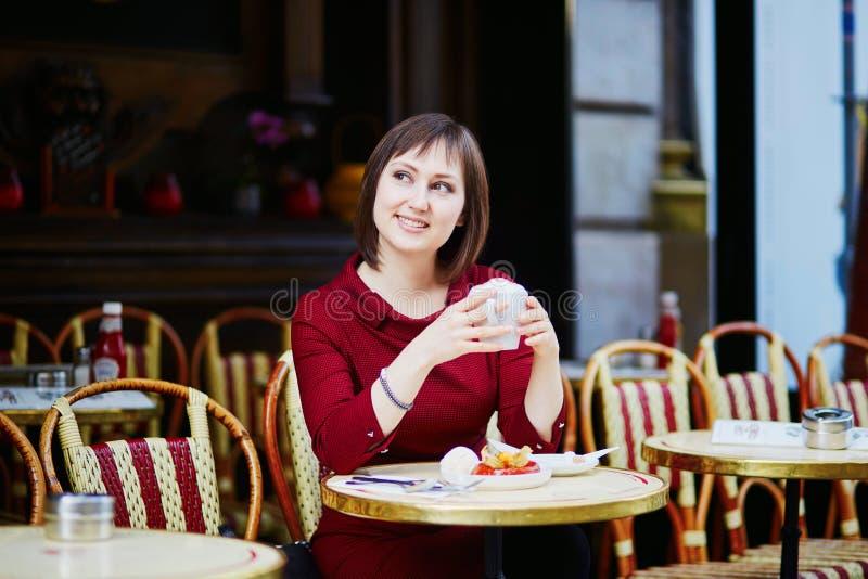 Café bebendo da mulher francesa no café exterior em Paris, França fotografia de stock