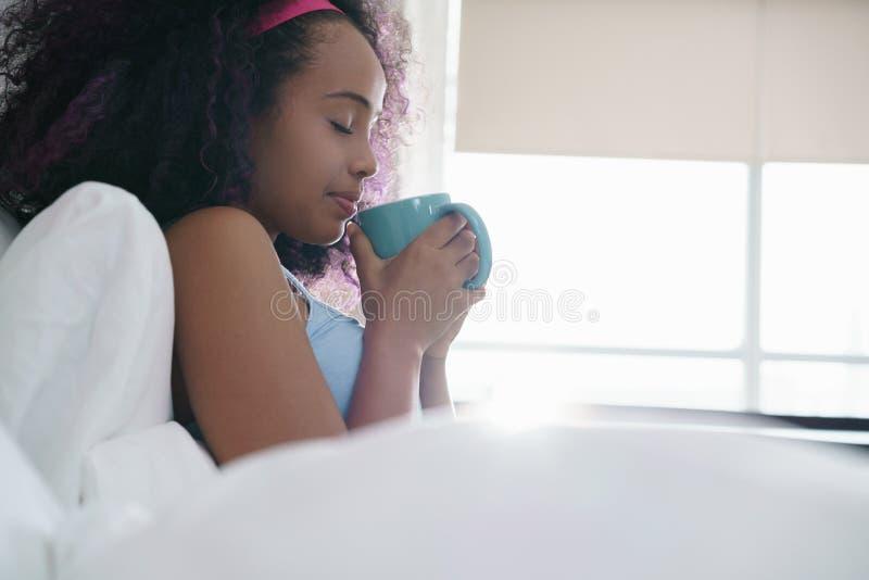 Café bebendo da mulher negra no sorriso da cama fotos de stock royalty free
