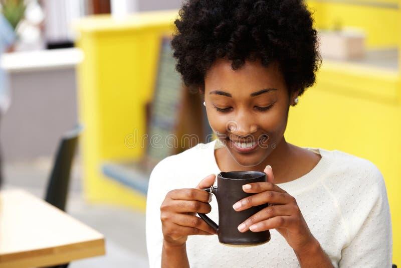 Café bebendo da mulher negra nova feliz fotos de stock