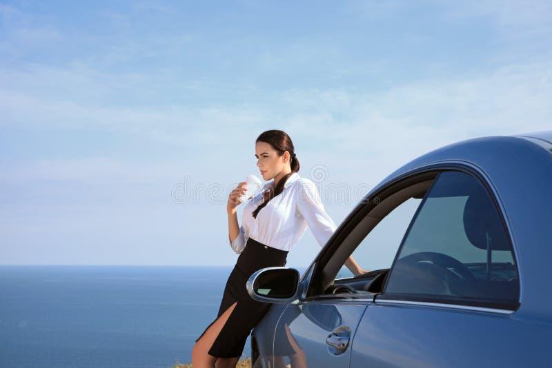 Café bebendo da mulher séria do homem de negócios perto do carro imagens de stock