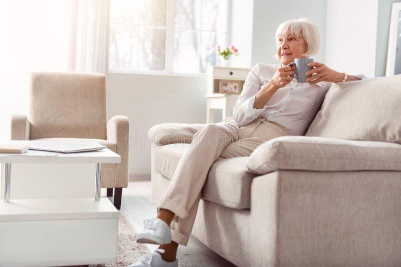 Café bebendo da pequeno mulher idosa em sua sala de visitas fotografia de stock