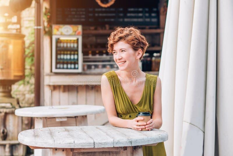Café bebendo de sorriso bonito da mulher no café Retrato da mulher em um bar que bebe o cappuccino quente Mulher com o copo do co imagens de stock