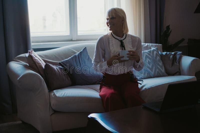 Café bebendo de sorriso da menina no sofá pela janela foto de stock