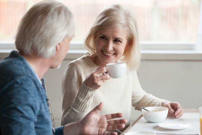 Café bebendo de sorriso da mulher madura que escuta o homem idoso Ta imagens de stock royalty free