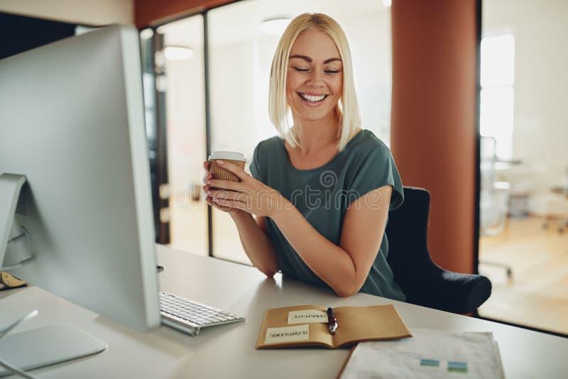 Café bebendo de sorriso da mulher de negócios nova ao trabalhar nela foto de stock