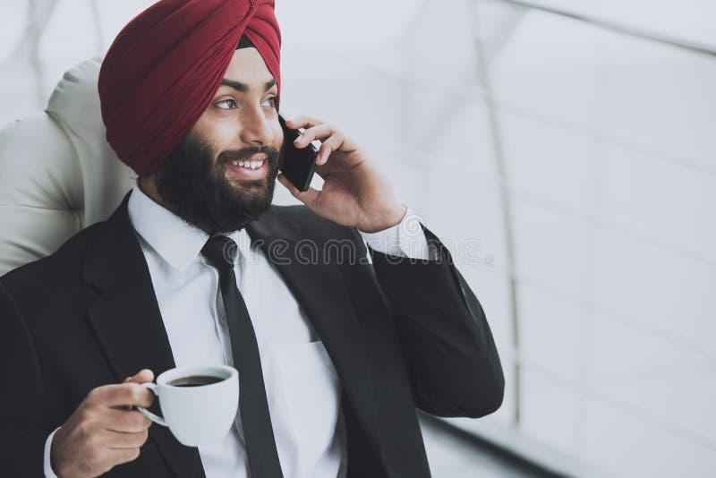 Café bebendo de sorriso do homem de negócios indiano fotografia de stock royalty free