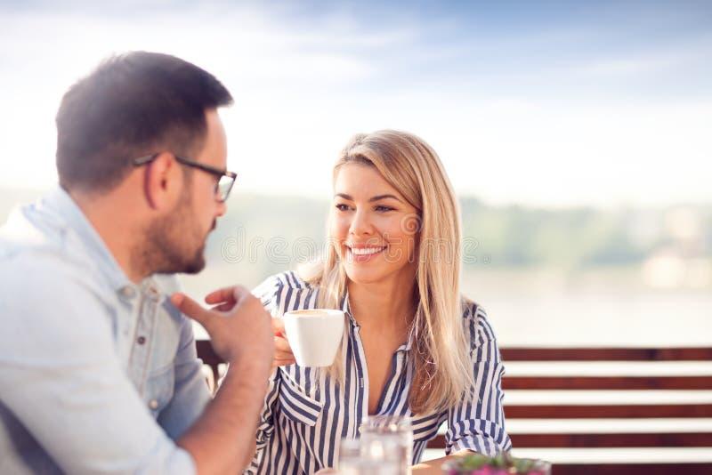 Café bebendo de sorriso novo dos pares fotografia de stock