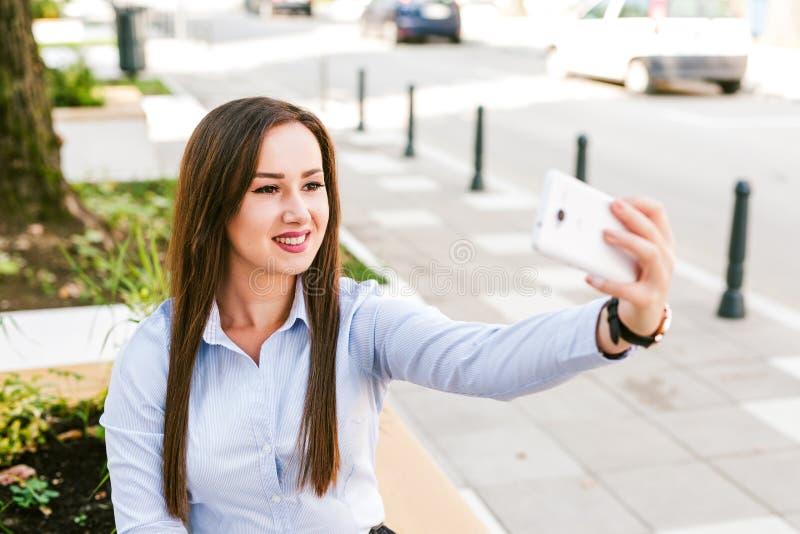 Café bebendo de Taking Selfie While da mulher de negócios bonita nova exterior fotografia de stock royalty free