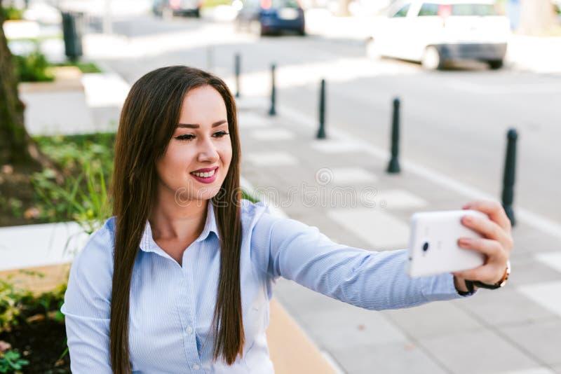 Café bebendo de Taking Selfie While da mulher de negócios bonita nova exterior imagens de stock royalty free