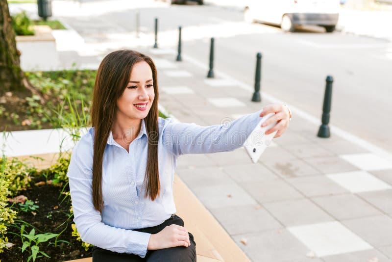 Café bebendo de Taking Selfie While da mulher de negócios bonita nova exterior imagem de stock royalty free