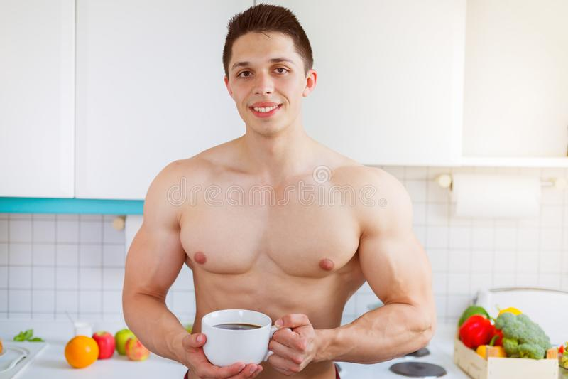 Café bebendo descamisado do homem novo do halterofilista na cozinha m imagens de stock royalty free