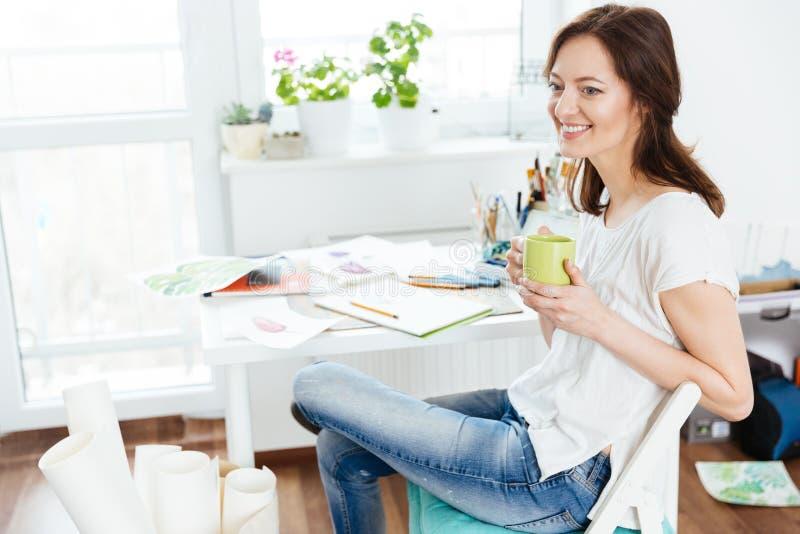 Café bebendo do artista feliz relaxado da mulher na oficina fotografia de stock