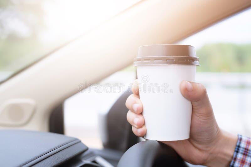 Café bebendo do copo de papel do homem de negócio da pessoa dos povos de quente à disposição ao conduzir em um carro na luz solar fotografia de stock
