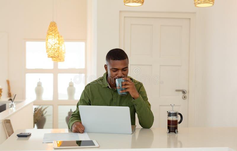 Café bebendo do homem ao trabalhar no portátil na mesa de jantar na cozinha na casa confortável imagens de stock royalty free