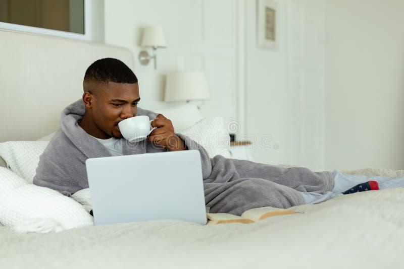 Café bebendo do homem ao usar o portátil na cama no quarto fotografia de stock royalty free
