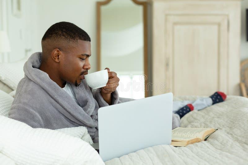 Café bebendo do homem ao usar o portátil na cama no quarto imagem de stock