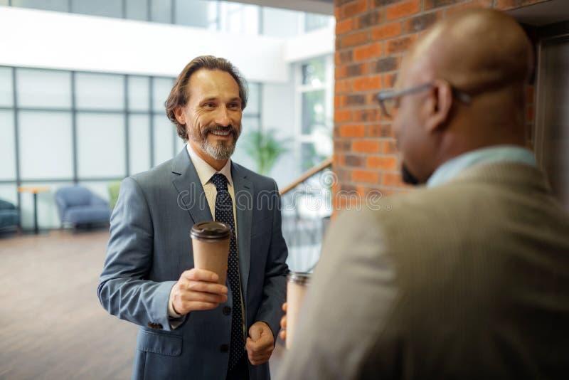 Café bebendo do homem de negócios ao esperar o elevador com colega imagens de stock