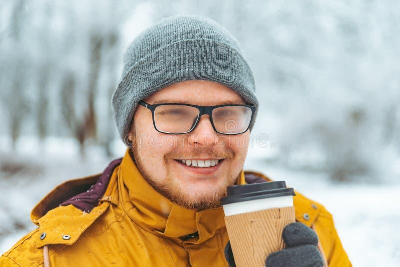 Café bebendo do homem a ir fora no dia de inverno nevado os vidros misted fotos de stock